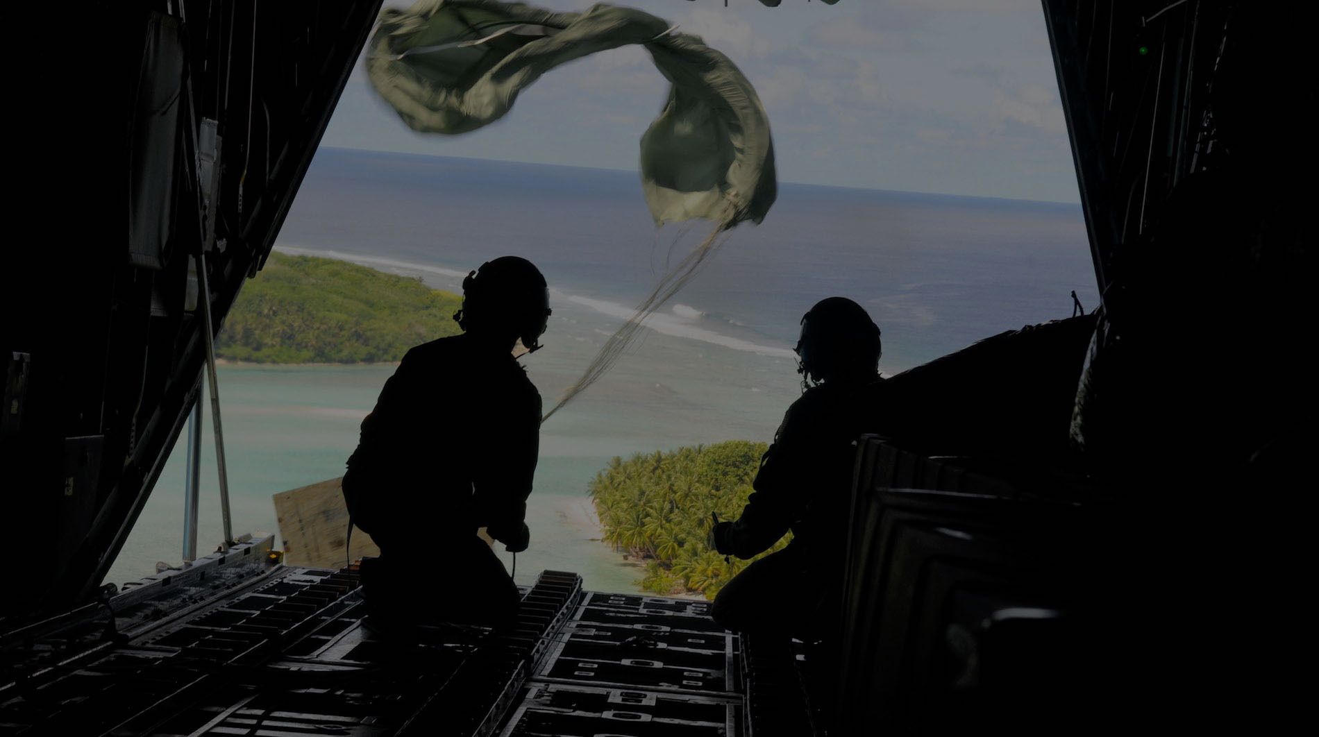 Airmen from the 36th Airlift Squadron, Yokota Air Base, Japan, watch as the parachute deploys and a box of humanitarian goods travels to the Yap Islands below during Operation Christmas Drop, Dec. 14, 2010. Operation Christmas Drop is the Air Force's longest-running humanitarian which began in 1952. What started as a WB-50 aircrew returning to Guam on its final flight before Christmas has turned into the longest running humanitarian campaign in the history of the U.S. Air Force and the entire world. (U.S. Air Force photo/Senior Airman Nichelle Anderson)